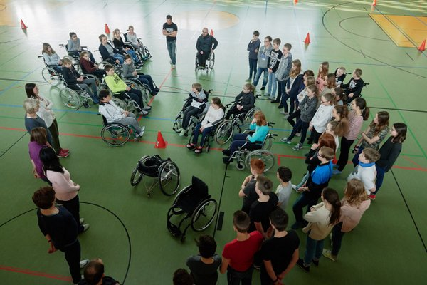 Basketballspieler mit und ohne Rollstuhl im Kreis